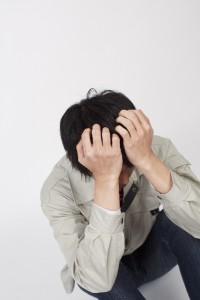頭を抱える作業着の男性