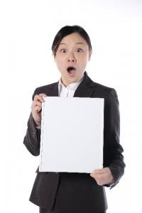 書類を手にびっくりする女性